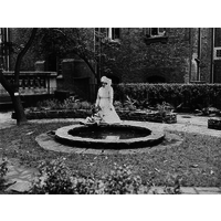 Nurse and child by pond in National Hospital garden